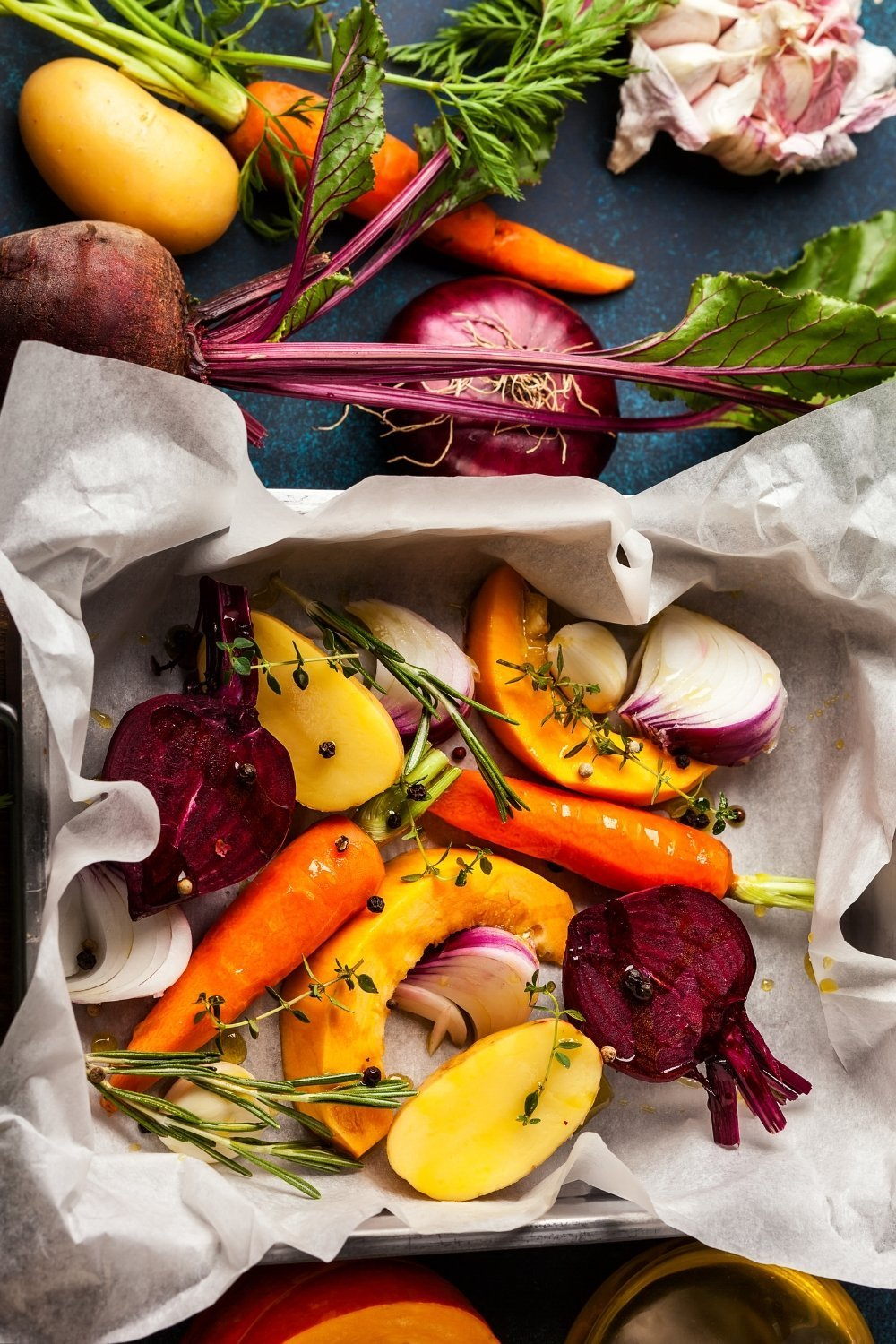 squashes, carrots, potatoes, and onions roasting in a pan