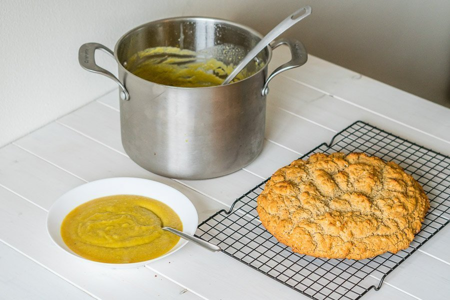 Side view of a sunny yellow bowl of golden beet soup beside a fresh loaf of gluten-free Irish Soda Bread cooling on a rack.